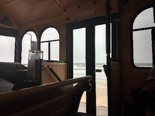 wooden interior and arched windows of a trolley looking out to sea