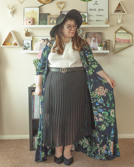 An outfit consisting of a black wide brim hat, green floral maxi dress worn as jacket over a white blouse with a tie neck tucked into a black pleated midi skirt and black pointed toe slingback flats.