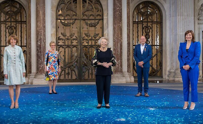Princess Beatrix of the Netherlands wore a navy blue floral tulip print blouse, and navy blue trousers. Gold necklace