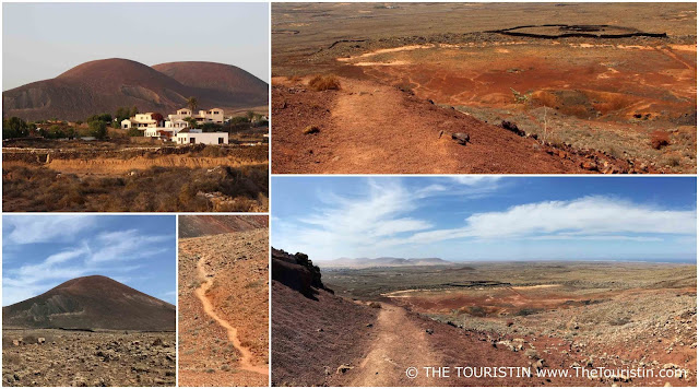 Village with white cubic houses in front of a volcano. Arid landscape.