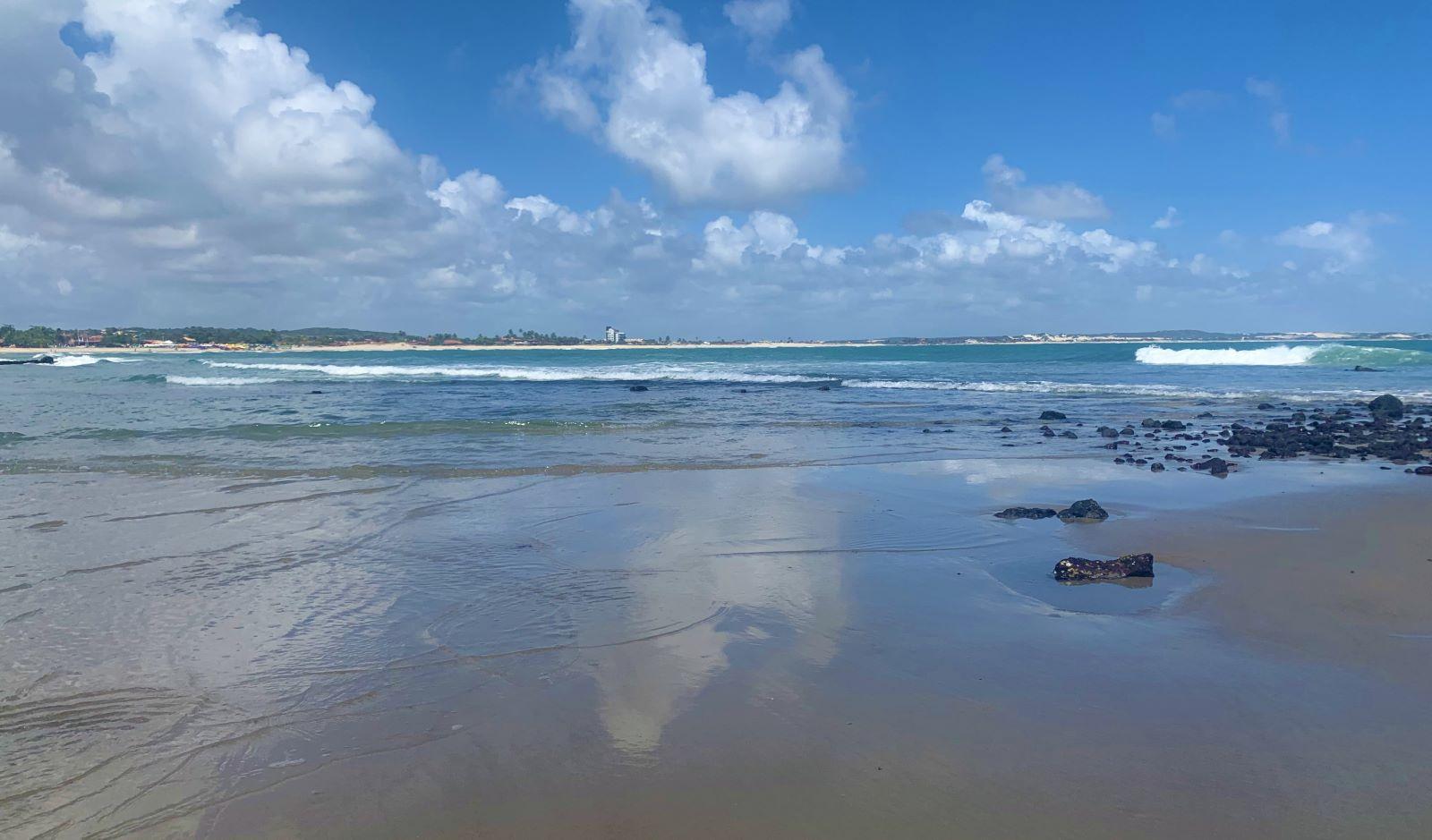 praia com aguas calmas e rochas nas orla