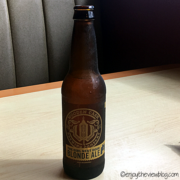 bottle of The Girl Next Door blonde ale from The Wooden Cask - sitting on a table