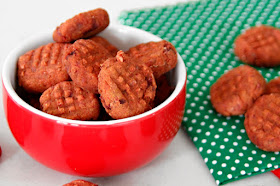 Bowl of red dog treats on a green and white polka dot napkin