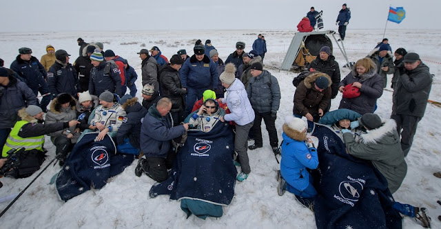 Expedition 57 crew members Alexander Gerst of ESA (European Space Agency), left, Sergey Prokopyev of Roscosmos, center, and Serena Auñón-Chancellor of NASA sit in chairs outside the Soyuz MS-09 spacecraft after they landed in a remote area near the town of Zhezkazgan, Kazakhstan on Thursday, Dec. 20, 2018. Auñón-Chancellor, Gerst, and Prokopyev are returning after 197 days in space where they served as members of the Expedition 56 and 57 crews onboard the International Space Station. Photo Credit: (NASA/Bill Ingalls)