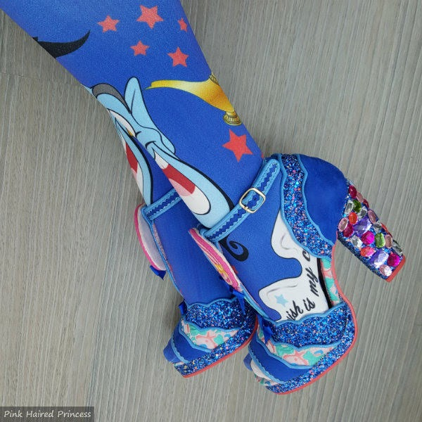 jewel heeled sandals on feet with printed Disney tights
