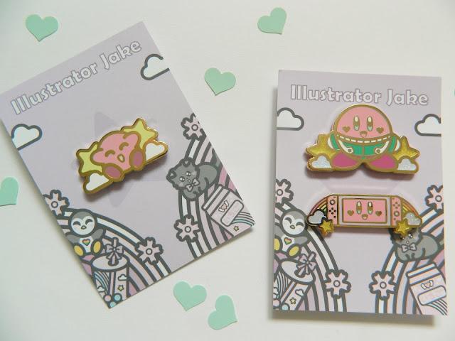 A photo showing three Nintendo Kirby enamel pins by artist Illustrator Jake