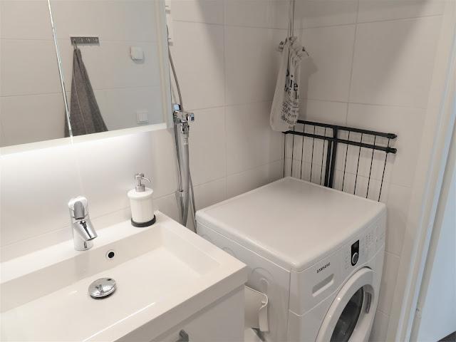 Pesukone kuivaustelineineen ja pyykkipoikapusseineen