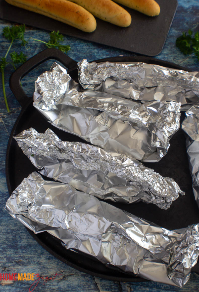 Baked foil packets of fish out of the oven on a black baking sheet.