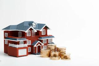 Imagem de uma prédio de concreto pintado de vermelho com teto cinza, janelas e portas brancas e um punhado de moedas douradas em frente representando artigo sobre reajuste de aluguel.