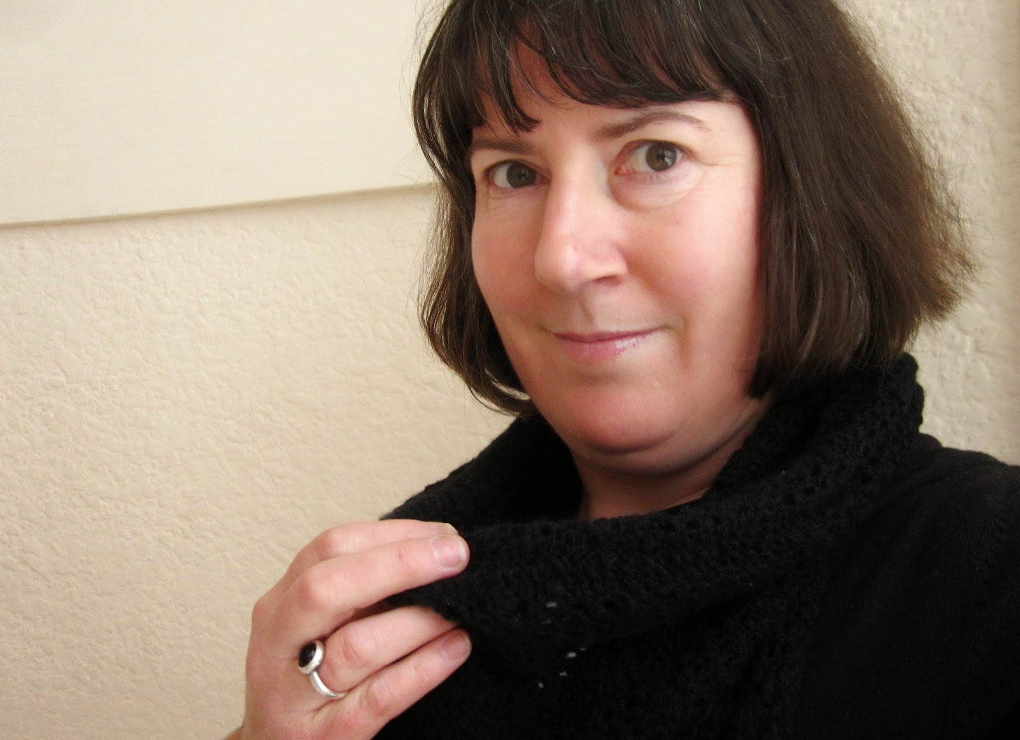 Woman holding a black knitted lacey scarf around her neck.