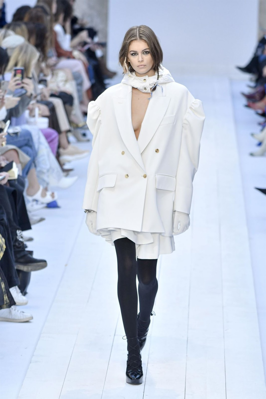 Braless Kaia Gerber sports a plunging oversized suit jacket at Max Mara MFW show