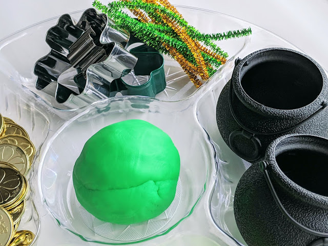 St. Patrick's Day play dough tray for kids with plastic gold coins, cauldron and shamrock cookie cutters
