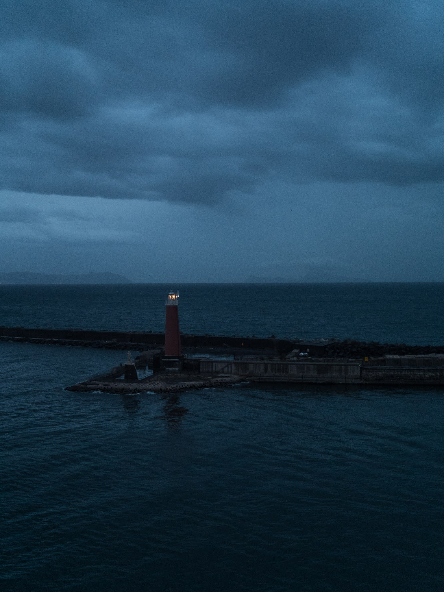 The lighthouse on Molo di San Vincenzo in the port of Naples at dawn