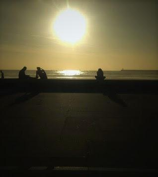 pessoas admirando o pôr do sol