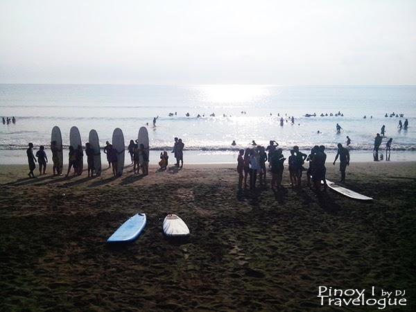 Surfers lining Baler's beach