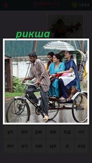 водитель рикши везет пассажиров трех женщин по дороге