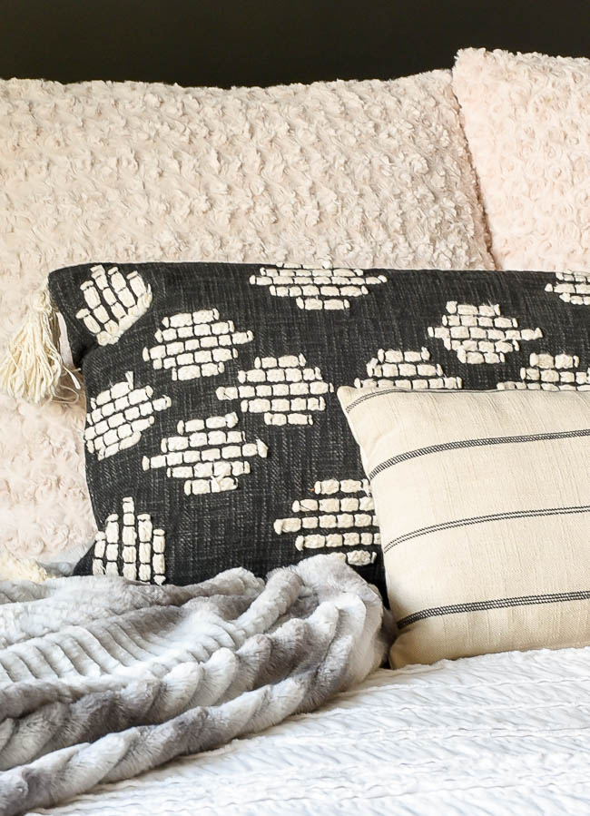Neutral textured throw pillows on bed