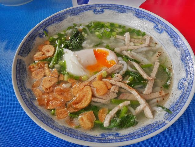 a bowl of laotian noodle soup with a fried egg, pork, and fried garlic