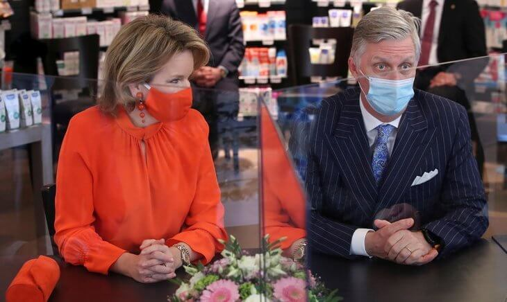 Queen Mathilde wore an orange color silk top and mask from Natan, and a beige wool coat by Natan. the pharmacy Pharma Haelvoet in Evere