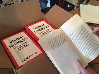 Hands holding open a copy of the book Insurgent Supremacists by a box full of copies of the book.