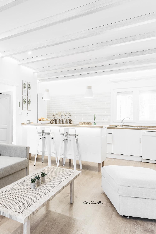 Un salón abierto y luminoso que combina paredes y techo blanco, suelo parquet claro y mesa de centro y sillas de mimbre  - Foto: Ale Favetto