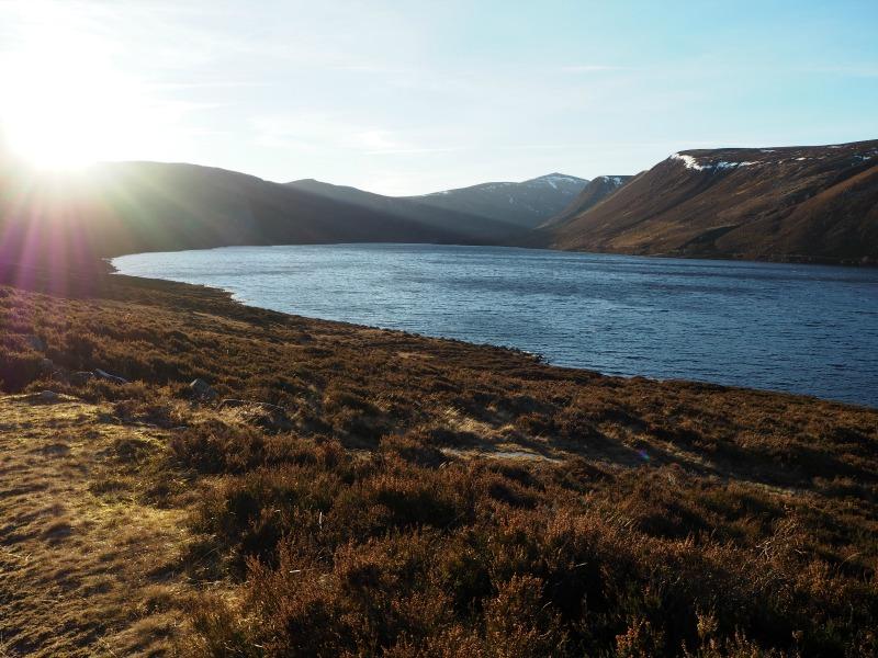 Sun peeking out behind mountains surrounding Lock Muick in Aberdeenshire