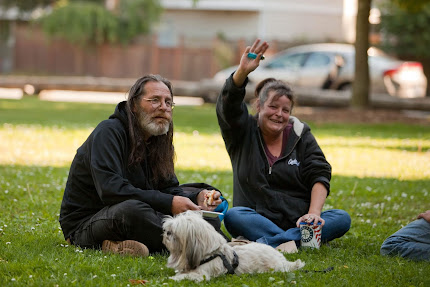 a smiling couple sit on the lawn