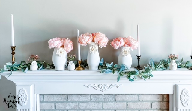 six white vases pink peonies white paper flowers fireplace mantel