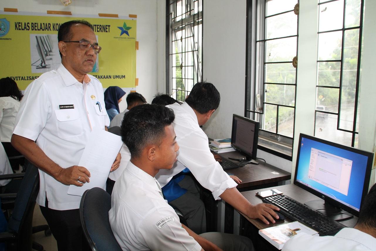 Kepala Dinas Perpustakaan Kabupaten Labuhanbatu  saat menyaksikan para peserta mengikuti pelatihan Komputer dan Internet