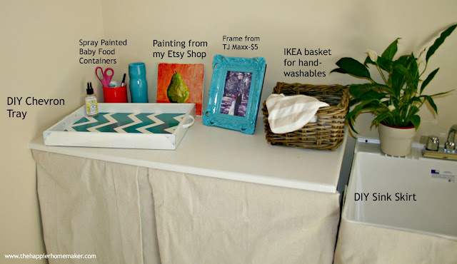A laundry room with no sew canvas drop cloth skirts covering a sink and shelves with decor on top of the shelf