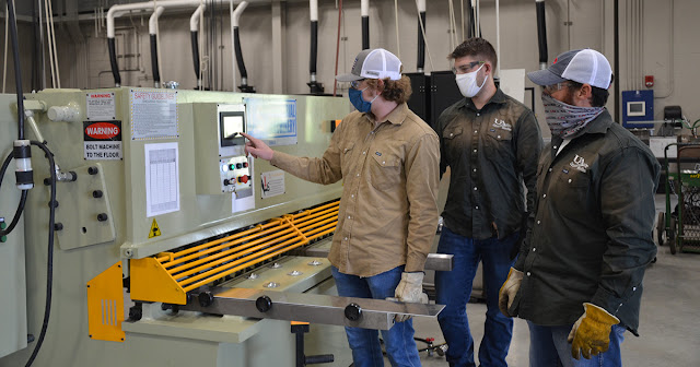 A students taps on the welding shear's touch pad as another student and an instrctor watches