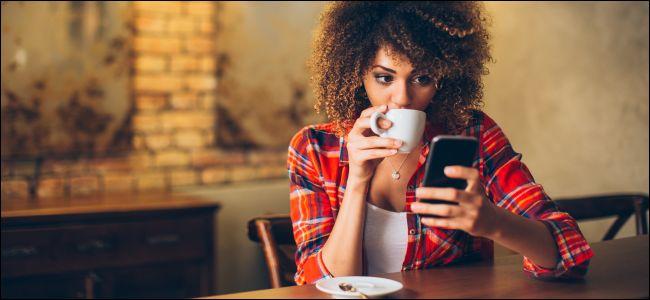 امرأة جالسة على طاولة تنظر إلى هاتف ذكي وتشرب القهوة.