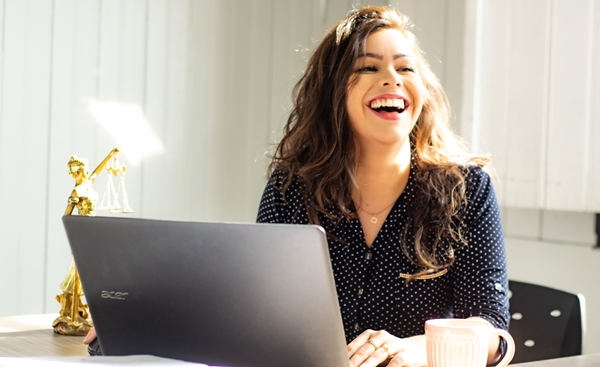 Mulher branca de cabelos cacheados #GirlBoss em frente ao computador sorrindo