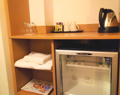 The fridge and kettle area in a Novotel hotel room.