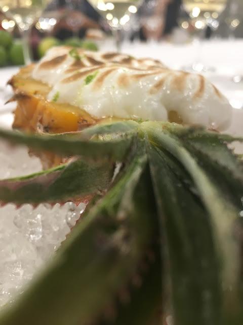 Postre del hotel tres reyes  Piña rellena de sorbete de te verde, bizcocho empapado de sake y merengue de Lima.