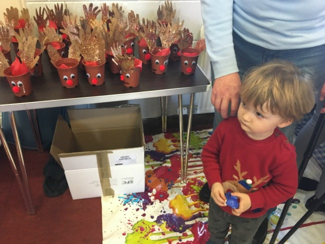 toddler-in-reindeer-jumper-stood-next-to-craft-made-reindeer-from-flower-pots
