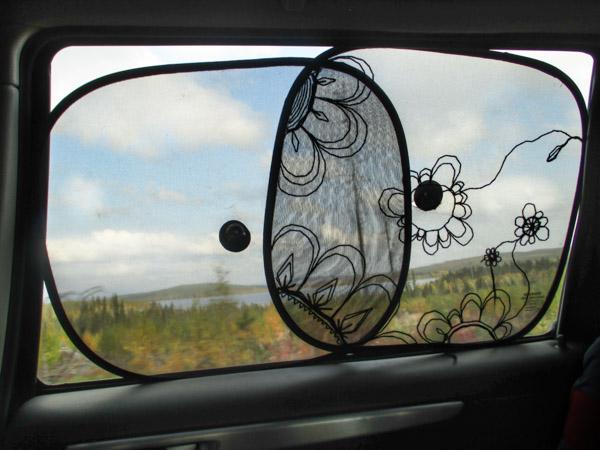 Kirjottu aurinkosuoja autossa ja Yli-Muonion maisemia