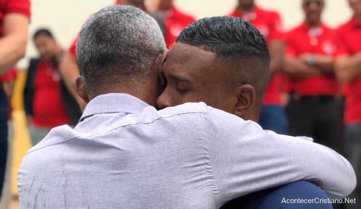 Padre abraza a su hijo tras bautismo