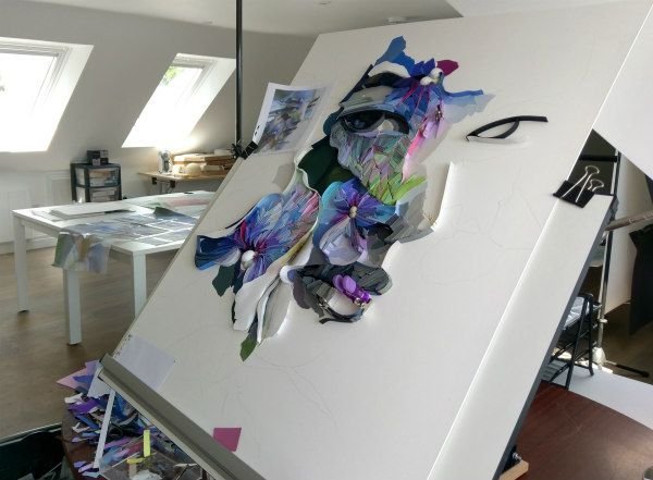 light-filled studio includes a large easel holding work in progress of a woman's face composed of paper strips