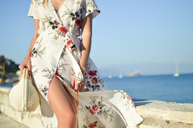 woman walking on beach wearing a white floral dress