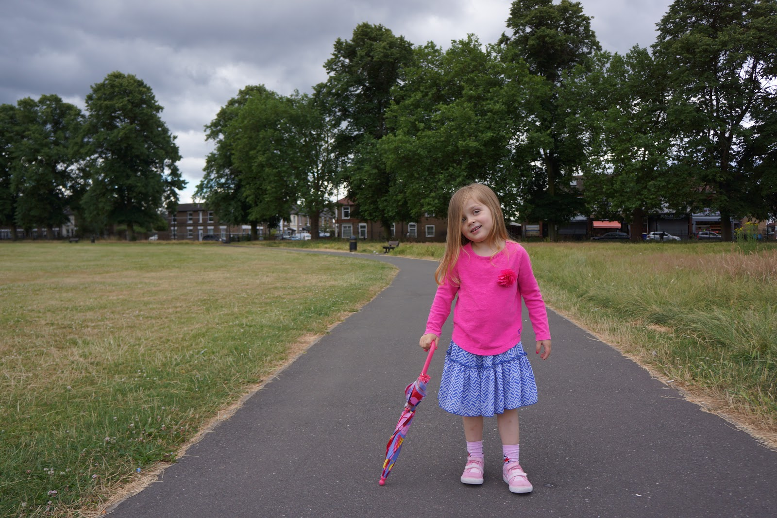 girl in bright pink Joules shirt in park