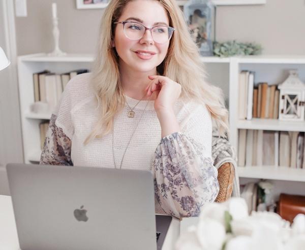 Mulher sentada de frente para o seu computador ao elaborar um bom currículo