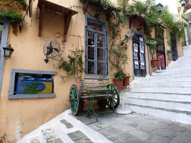 białe schody na których stoi dekoracyjna drewniana ławka z zielonymi kołami i zielonym stolikiem, ściany domów w kolorze brzoskwini z niebieskimi ramami okien, ulica Aten.