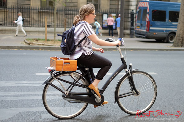 Woman in striped  top and dark pants rides a modern open framed bike with wooden tray on rear rack. Paris photos by Kent Johnson for Street Fashion Sydney.