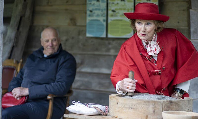 Queen Sonja wore a red wool cashmere cape coat, and white trousers