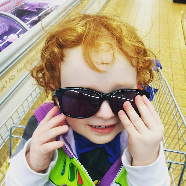 Redheaded toddler wearing oversized sunglasses whilst sitting in a supermarket trolley