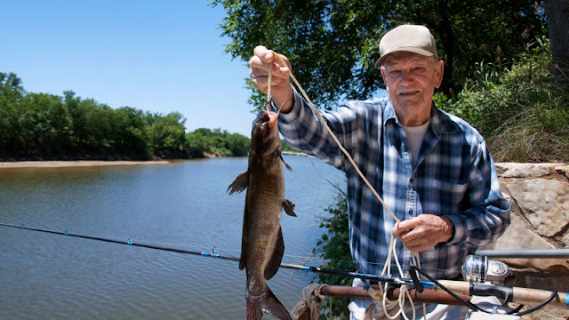 Elderly man with fish on a line