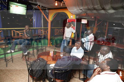 Kenyan Men Seated Together In A Bar Watching TV