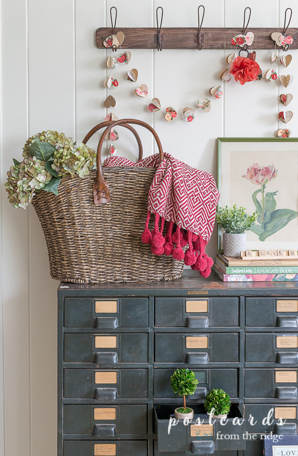vintage metal cabinet with woven basket and valentine's day decor
