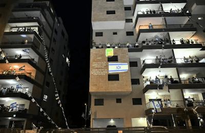 Das varandas dos prédios, israelenses cantam Hatikvah pelos soldados mortos em conflitos